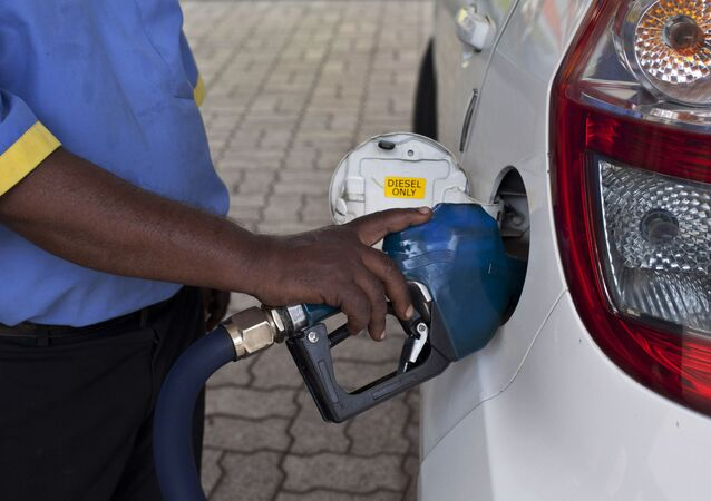 A man fills diesel in a car at a fuel station in New Delhi, India, Sunday, Oct. 19, 2014. India freed diesel prices from government control Sunday while raising natural gas tariffs in the biggest-yet reform by Prime Minister Narendra Modi's government, as it aims to boost the country's economy and overhaul its energy sector.(AP Photo/Tsering Topgyal)