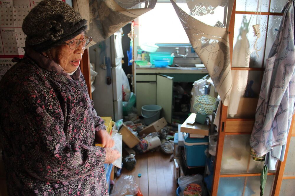 Japanese woman Taeko Naito stands looking at her shattered kitchen at her home in Soma, Fukushima Prefecture on 14 February 2021, after a 7.3-magnitude earthquake struck off Japan's east coast on 14 February.