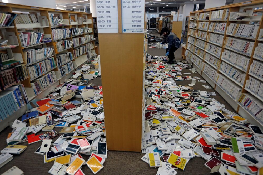 A member of staff at the library tries to restore order after the books were shaken from their shelves by a strong earthquake at Iwaki City library in Iwaki, Fukushima Prefecture, Japan, 14 February 2021.