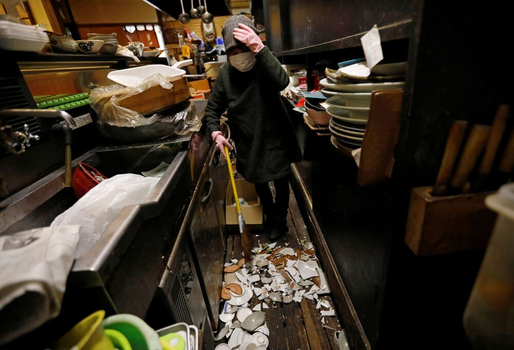 Mitsue Hisa, 70, the owner of a Japanese izakaya pub, cleans up broken dishes at her shop after a strong quake in Iwaki, Fukushima Prefecture, Japan, 14 February 2021.