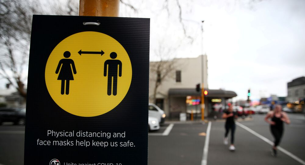 FILE PHOTO: People jog past a social distancing sign on the first day of New Zealand's new coronavirus disease (COVID-19) safety measure that mandates wearing of a mask on public transport, in Auckland, New Zealand, August 31, 2020.  REUTERS/Fiona Goodall