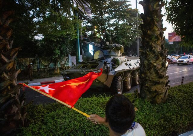 A man waves a flag next to an armoured vehicle during a protest against the military coup, in Yangon, Myanmar, 14 February 2021.