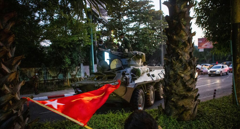 A man waves a flag next to an armoured vehicle during a protest against the military coup in Yangon Myanmar 14 February 2021