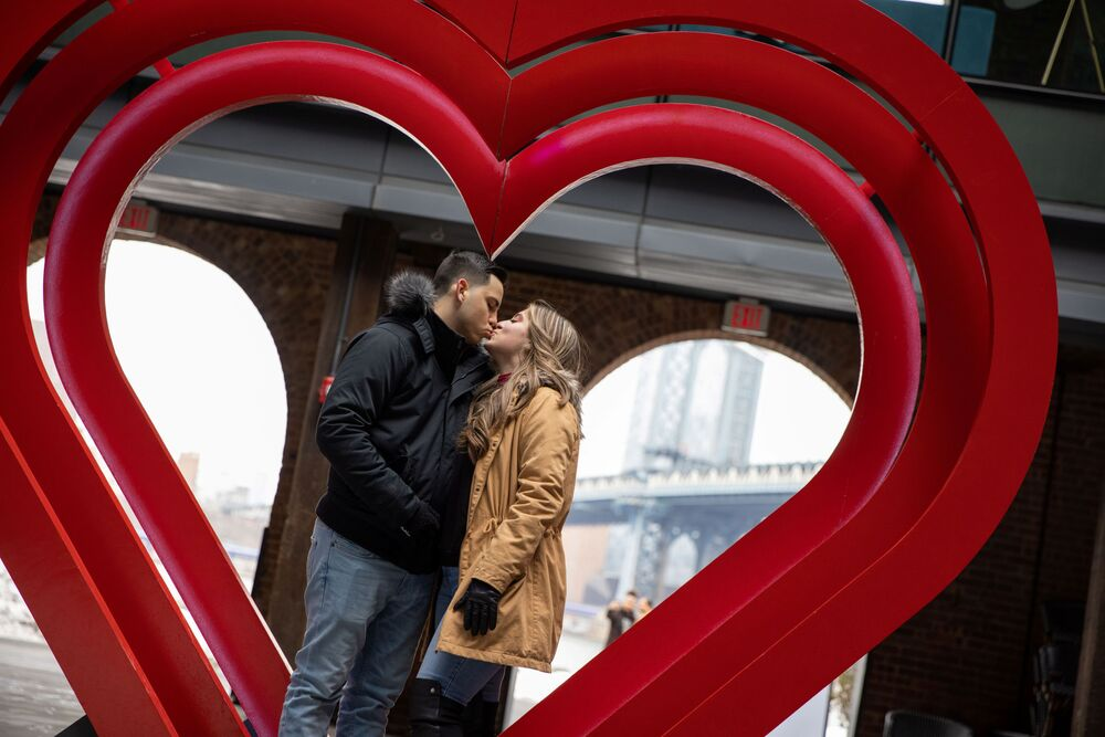 Angelina Sarge and Richard Rubido kiss in front of a heart sculpture in DUMBO on Valentine's Day during the coronavirus disease pandemic, in the Brooklyn borough of New York City, New York, U.S., 14 February 2021.