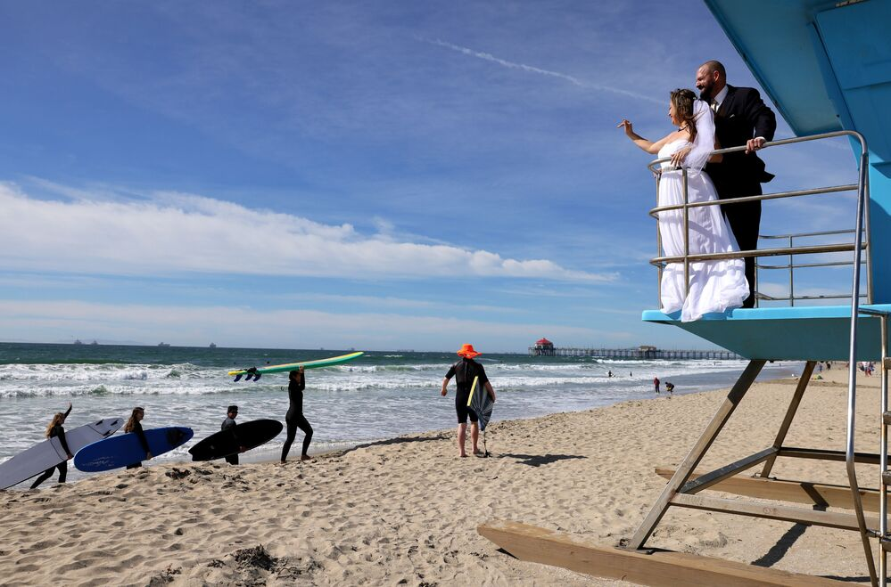Lorena and Steven James wave to surfers while posing for photos on a lifeguard tower after they were married on the beach on Valentine's Day on 14 February 2021 in Huntington Beach, California. The bride said they decided to have a small wedding on the beach in order maintain safety amid the COVID-19 pandemic. She said, 'We don't let the pandemic stop us from living life.'