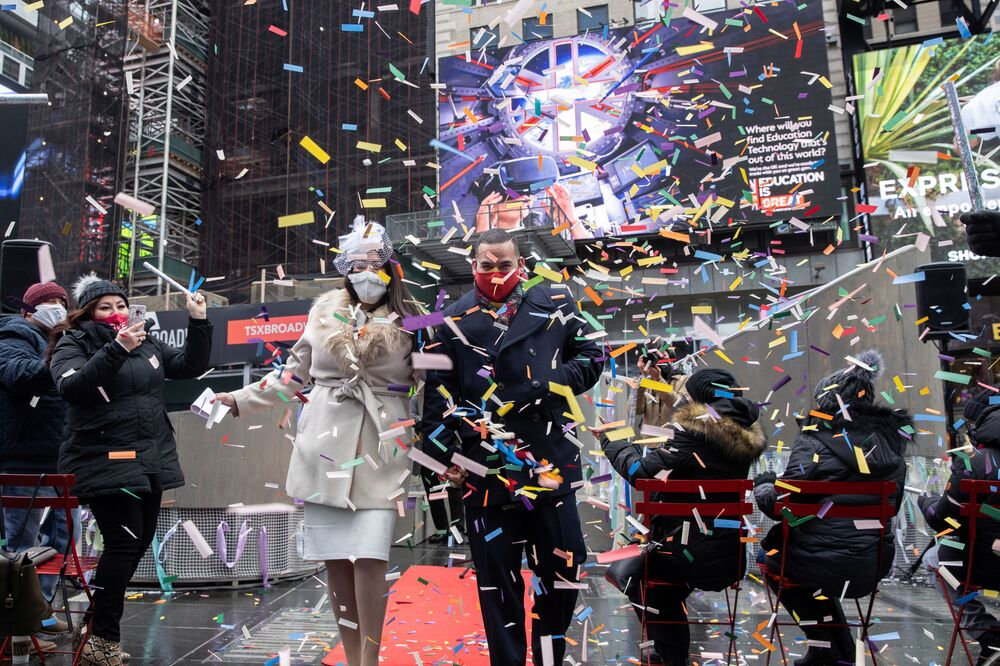 Denise and Robert Marte, wearing protective masks, walk down a red carpet after exchanging their vows at their Valentine's Day wedding ceremony in Times Square in Manhattan, New York City, New York, US, 14 February 2021.