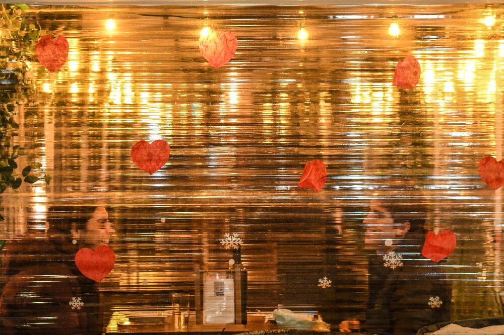 A couple have dinner behind outdoor seating screening on Valentine's Day on 14 February 2021 in the Little Italy neighborhood in New York City. New York City resumed indoor dining over the weekend at 25 percent capacity, with restaurant hours being extended from 10 p.m. to 11 p.m. beginning today.