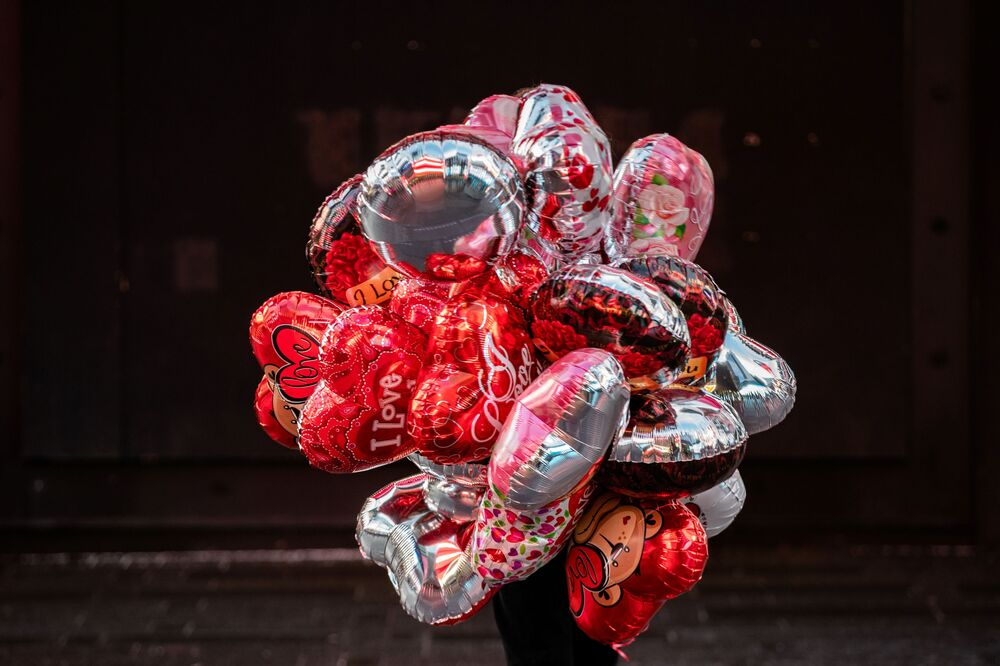 A person carries balloons on Valentine's Day in Times Square in Manhattan, New York City, New York, 14 February 2021.
