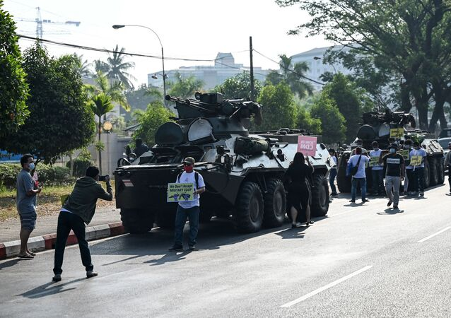 Protesters gather next to military vehicles parked along a street in downtown Yangon on February 15, 2021, the morning after Myanmar's military cut the nation's internet and deployed extra troops around the country.