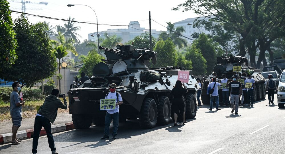 Protesters gather next to military vehicles parked along a street in downtown Yangon on 15 February 2021, the morning after Myanmar's military cut the nation's internet and deployed extra troops around the country.