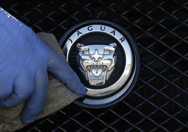 FILE - In this file photo dated Wednesday, Sept. 28, 2016, a worker polishes a Jaguar logo on a car at a Jaguar dealer outlet in London