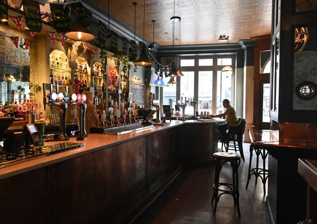 A single customer sits at the bar in a near-empty pub in central London on March 17, 2020 after the UK government announced stringent social distancing advice including avoiding pubs and restaurants as a measure to kerb the spread of novel coronavirus COVID-19