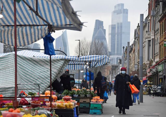 FILE PHOTO: People shop at market stalls, with skyscrapers of the CIty of London financial district seen behind, amid the coronavirus disease (COVID-19) pandemic, in London, Britain, January 15, 2021. REUTERS/Toby Melville/File Photo