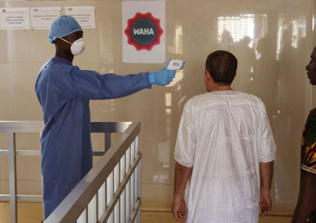 A health worker, center, takes the temperature of people to see if they might be infected by the Ebola virus inside the Ignace Deen government hospital in Conakry, Guinea, Friday March 18, 2016