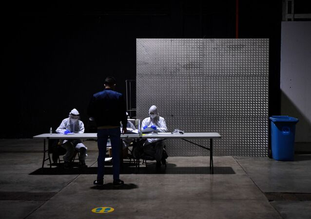 Officials wear Personal Protective Equipment (PPE) as a person casts his ballot during the voting period assigned for those infected with COVID-19 at a polling station in L'Hospitalet de Llobregat during regional elections in Catalonia on February 14, 2021.