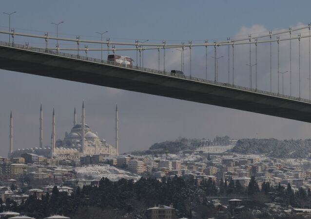 Vehicles cross Istanbul's July 15th Martyrs' Bridge, formerly known as Bosporus Bridge backdropped by the Camlica Mosque, covered in snow, Monday, Jan 18, 2021.
