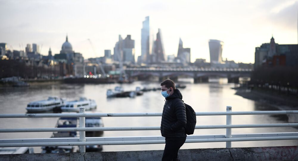 A man wearing a protective face mask walks across Waterloo Bridge, amid the coronavirus disease (COVID-19) outbreak in London, Britain, January 29, 2021.