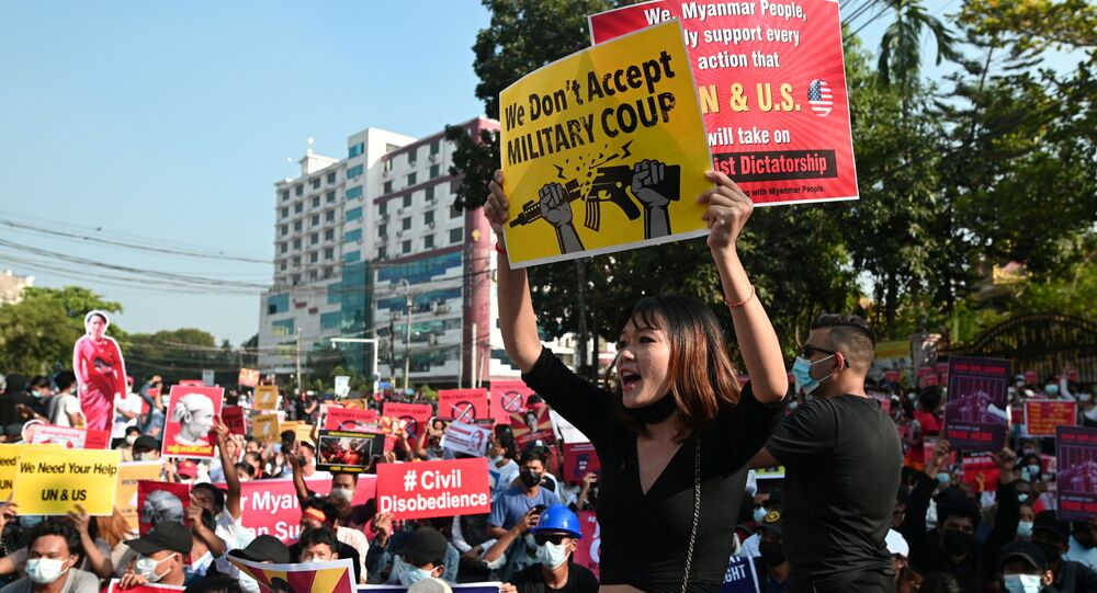 Demonstrators hold placards during a protest against the military coup in Yangon, Myanmar, February 15, 2021