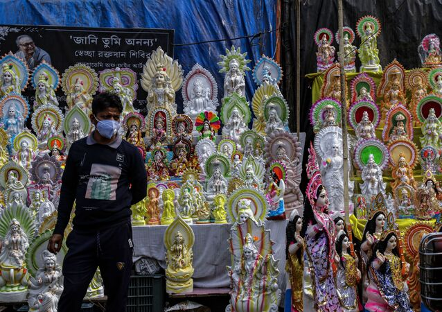 An Indian vendor wearing a face mask as a precaution against the coronavirus awaits customers as he sells clay images of Saraswati, the Hindu goddess of wisdom, ahead of the Basant Panchami festival in Kolkata, India, Sunday, 14 February 2021. The festival, which will be celebrated on 16 February, marks the arrival of spring.
