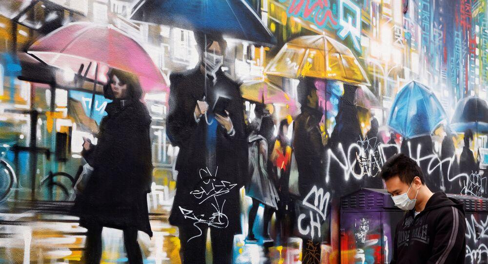 A man wearing a face mask walks past graffiti, amid the outbreak of the coronavirus disease (COVID-19) in London, Britain January 19, 2021