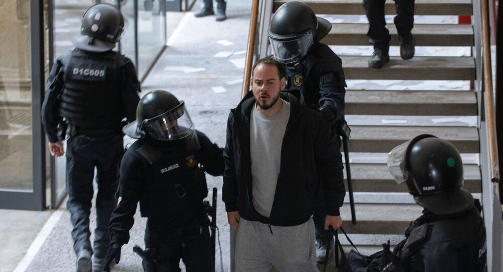 Spanish rapper Pablo Hasel reacts as he is detained by riot police inside the University of Lleida, after he was sentenced to jail time on charges including insulting the monarchy and glorifying terrorism, in Lleida, Spain February 16, 2021.