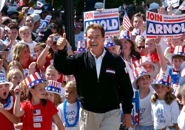 In this Oct. 5, 2003, file photo, Republican candidate for California governor Arnold Schwarzenegger walks up the steps to the state Capitol surrounded by children and waving to supporters during a campaign rally in Sacramento, Calif. California Gov. Gavin Newsom is facing a possible recall election as the nation's most populous state struggles to emerge from the coronavirus crisis