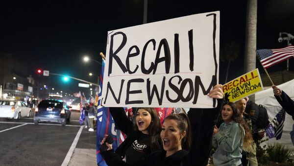 In this Nov. 21, 2020 file photo, demonstrators shout slogans while carrying a sign calling for the recall of Gov. Gavin Newsom during a protest against a stay-at-home order amid the COVID-19 pandemic in Huntington Beach, Calif - Sputnik International