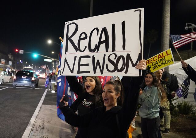 In this Nov. 21, 2020 file photo, demonstrators shout slogans while carrying a sign calling for the recall of Gov. Gavin Newsom during a protest against a stay-at-home order amid the COVID-19 pandemic in Huntington Beach, Calif