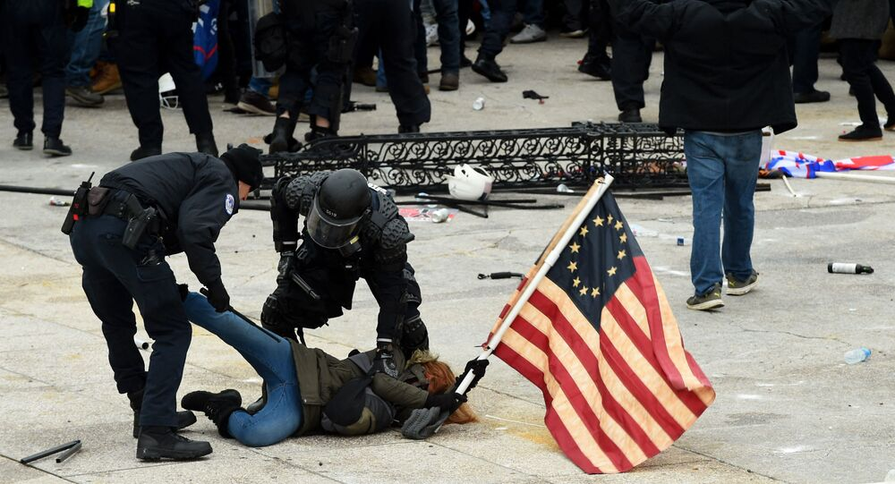 In this file photo taken on January 6, 2021, police detain a person as supporters of US President Donald Trump riot outside the US Capitol in Washington, DC. -