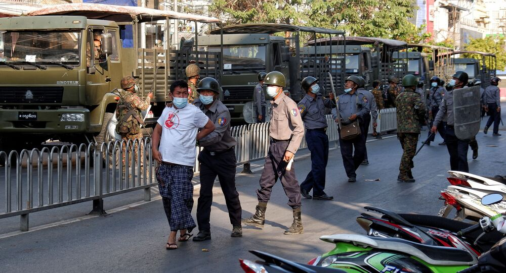 Police detains a man during a protest against the military coup in Mandalay, Myanmar, February 15, 2021.
