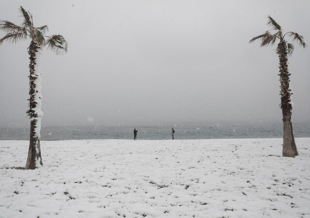 People take photos on a snow-covered beach during heavy snowfall in the suburb of Glyfada, in Athens, Greece, February 16, 2021.