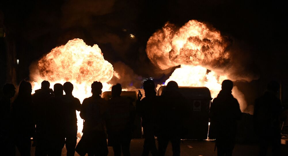 Flames rise from burning trash containers during clashes between protesters and Catalan regional police forces Mossos d'Esquadra after a demonstration against the arrest of Spanish rapper Pablo Hasel in Barcelona on February 16, 2021.