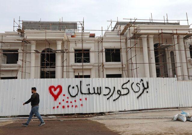 "A man walks past a graffiti reading in Kurdish Long live Kurdistan"", near the scene of a rocket attack in Arbil, the capital of the northern Iraqi Kurdish autonomous region, on February 16, 2021."