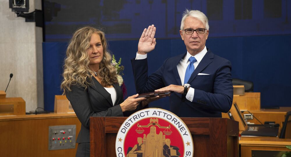 In this photo provided by the County of Los Angeles, incoming Los Angeles County District Attorney George Gascon is sworn in as his wife Fabiola Kramsky holds a copy of the Constitution during a mostly-virtual ceremony in downtown Los Angeles Monday, Dec. 7, 2020