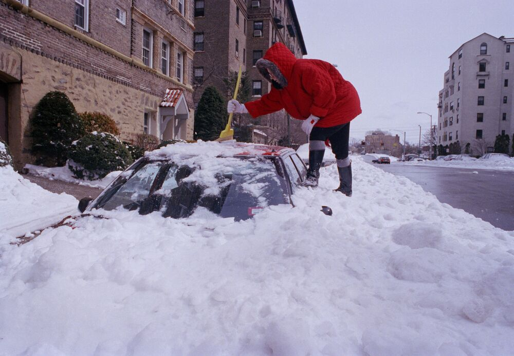 A woman climbs a mound of packed snow in Larchmont, N.Y. in 1993 as she tries to dig her car out of the snow.