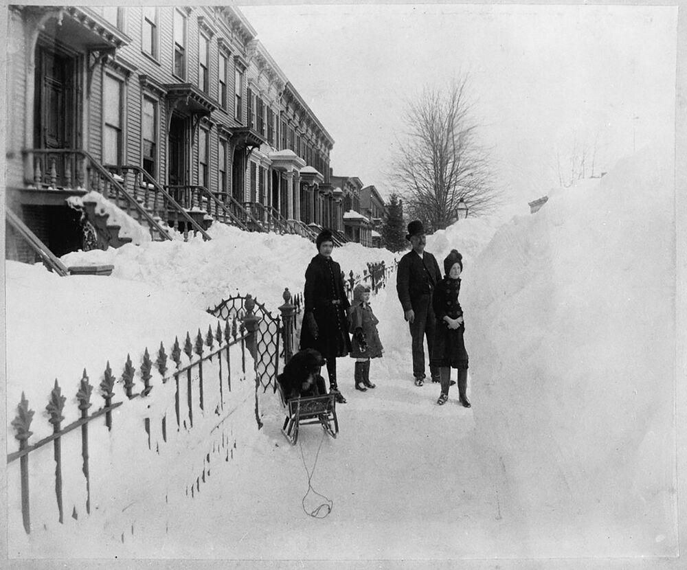 People in Brooklyn standing in front of huge piles of snow.