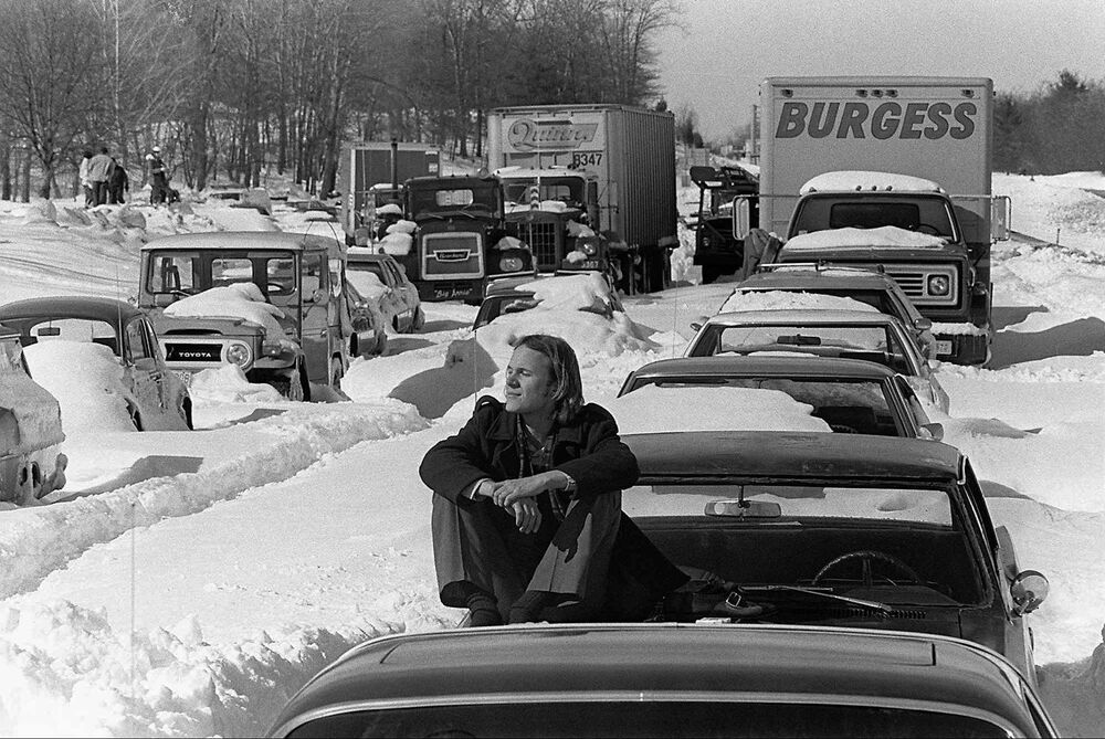 A man sits on the hood of his car, which is stuck in snow in Massachusetts on Route 128 in 1978.