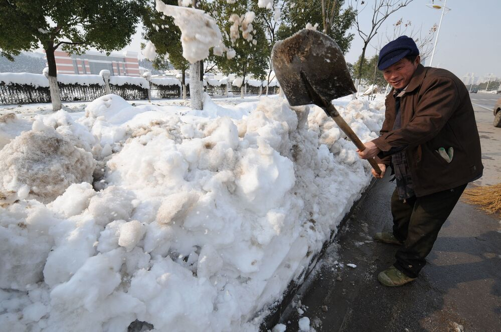 A Chinese worker shovels snow from the streets after heavy snowfalls in the eastern Chinese city of Nanjing, 31 January 2008.  China has dispatched its army to help millions of stranded people.