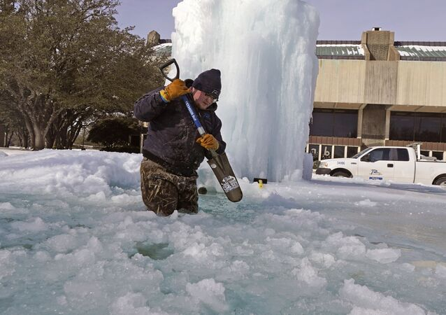 City of Richardson worker Kaleb Love breaks ice on a frozen fountain Tuesday, Feb. 16, 2021, in Richardson, Texas