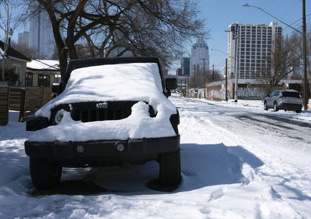 A parked Jeep is covered in snow Tuesday, Feb. 16, 2021, in Austin, Texas