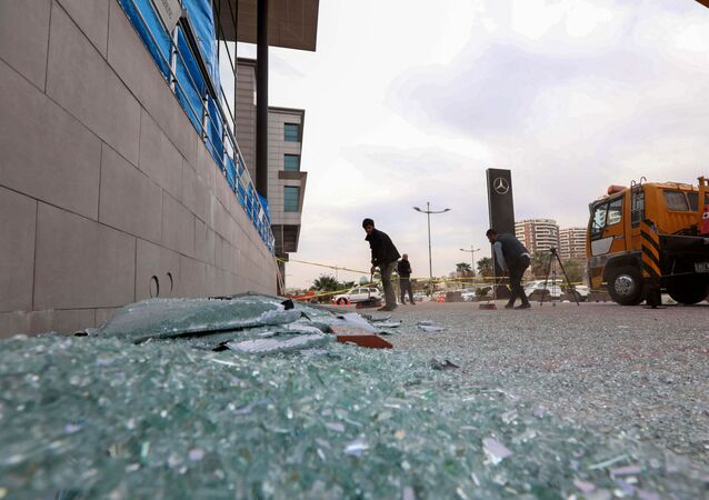 A worker cleans shattered glass on February 16, 2021 outside a damaged shop following a rocket attack the previous night in Arbil, the capital of the northern Iraqi Kurdish autonomous region