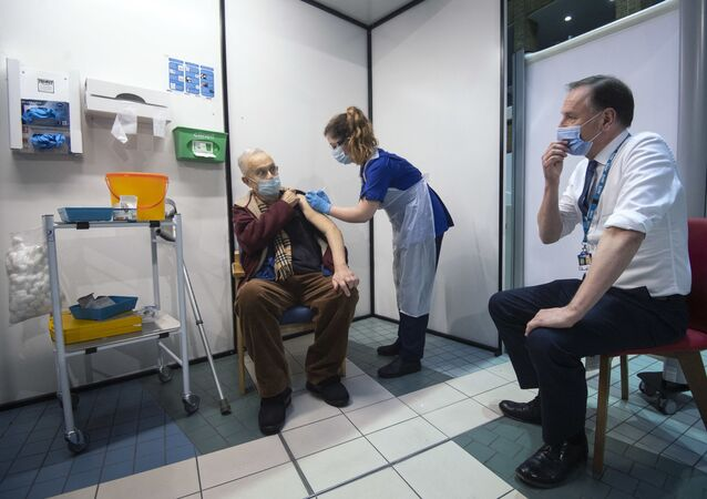 Simon Stevens (R), Chief Executive of the NHS, watches as a nurse (C) administers a dose of the Pfizer-BioNTech Covid-19 vaccine to Frank Naderer (L), 82, at Guy's Hospital in London on December 8, 2020 as the UK starts its biggest ever vaccination programme.