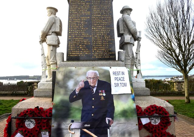 A giant photograph of Captain Tom Moore is added to a war memorial in the centre of Milford Haven, Wales, Britain, February 9, 2021.