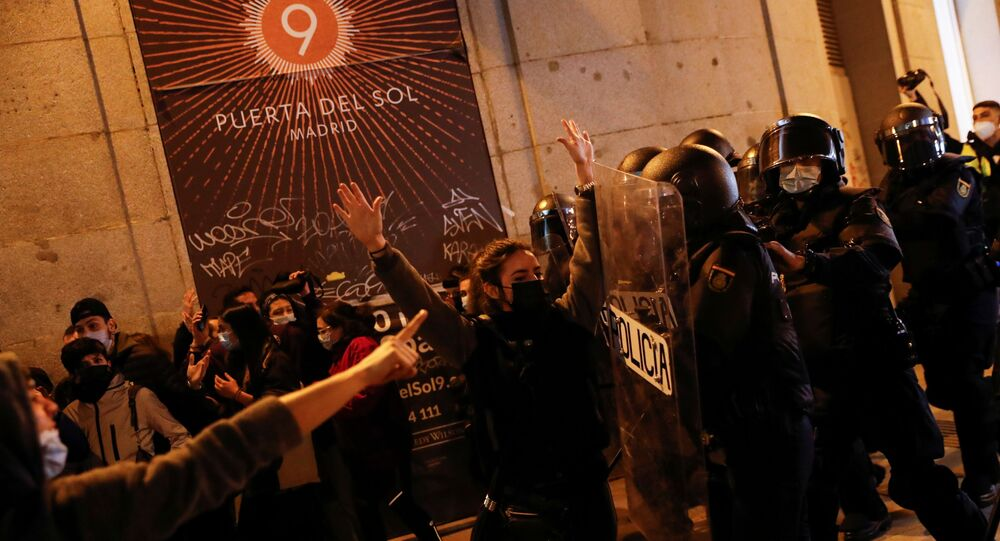 A person raises the hands in front of police officers as supporters of Catalan rapper Pablo Hasel protest against his arrest in Madrid, Spain, February 17, 2021.