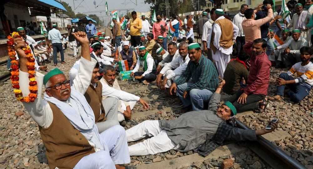 Farmers block a railway track to stop train services at Modi Nagar railway station as part of protests against farm laws, in Modinagar, Uttar Pradesh, India, February 18, 2021