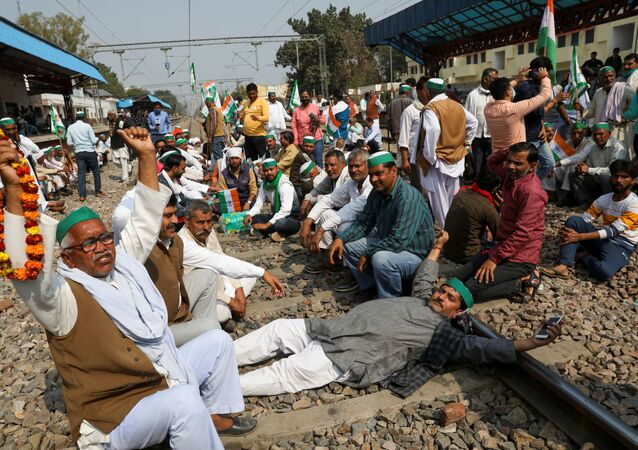 Farmers block the tracks to stop train services at Modi Nagar railway station as part of protests against farm laws, in Modinagar, Uttar Pradesh, India, 18 February 2021.
