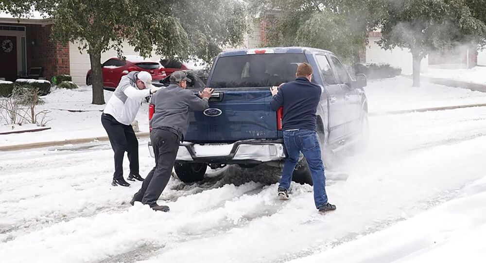 Residents help a pickup driver get out of ice on the road in Round Rock, Texas, on February 17, 2021, after a winter storm