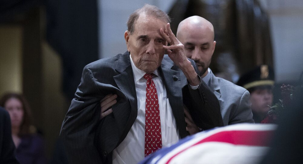 Former US Senator Bob Dole salutes before the flag-draped coffin of former US President George H. W. Bush at the US Capitol rotunda December 4, 2018 in Washington, DC.