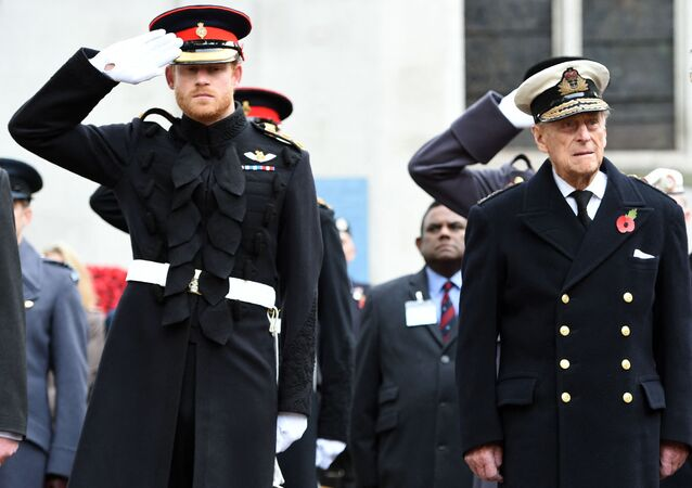 Britain's Prince Harry (L) salutes as he stands alongside his grandfather Britain's Prince Philip, Duke of Edinburgh, during their visit to the Field of Remembrance at Westminster Abbey in central London on November 10, 2016.