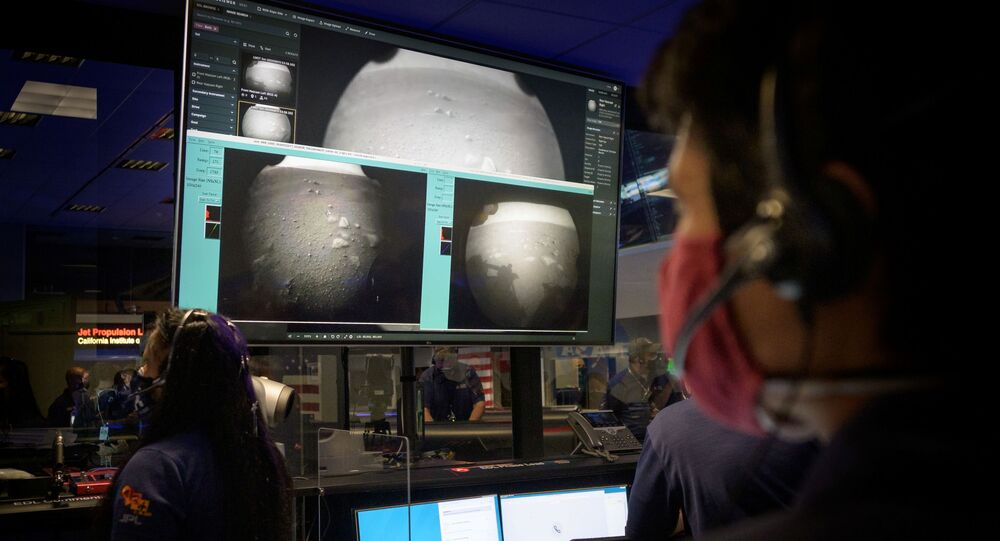Members of NASA's Perseverance Mars rover team watch in mission control as the first images arrive moments after the spacecraft successfully touched down on Mars, at NASA's Jet Propulsion Laboratory in Pasadena, California, U.S. February 18, 2021.